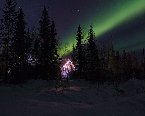 Bright green Aurora Borealis over a Swedish chalet