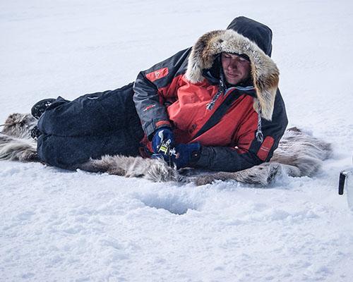 Man laying down ice fishing