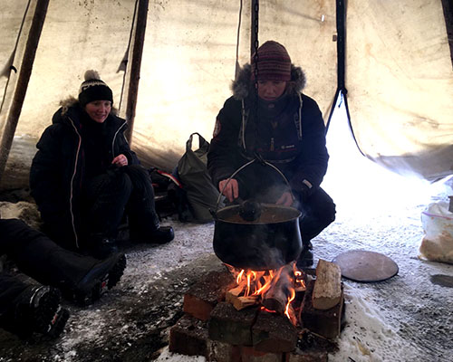 woman heating food over a camp fire in a tipi tent
