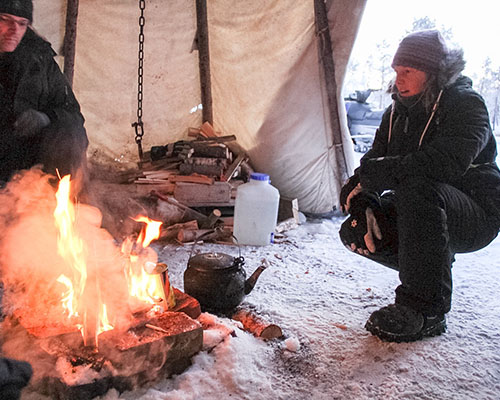 Lady with a roaring fire in a tipi tent
