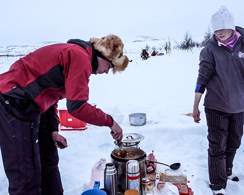 man making dinner over a camp stove in the snow