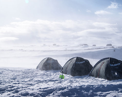 tents on a snowy scene cold
