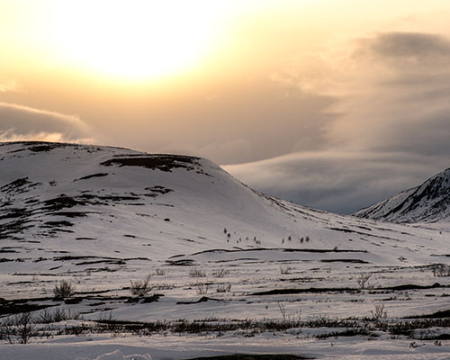 sun going down over a hilly arctic scene