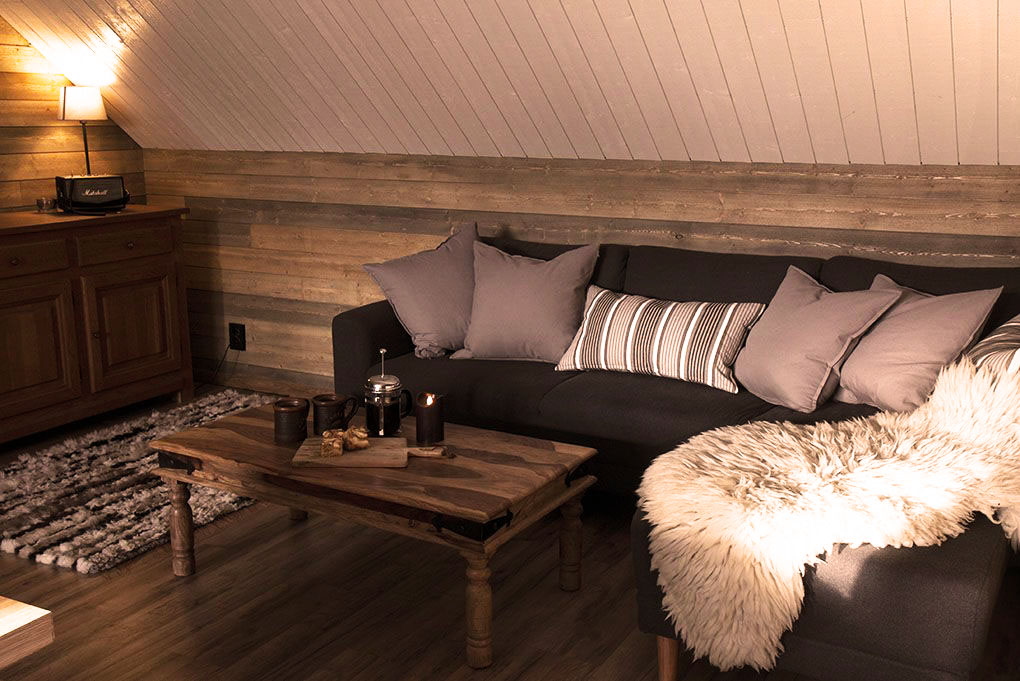 Lapland Sleddog Adventures guest lodge lounge with coffee and cake on a table
